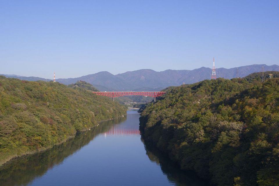 秋晴れの紺碧の空に木曽川の川面と鮮やか赤の城山大橋  border=