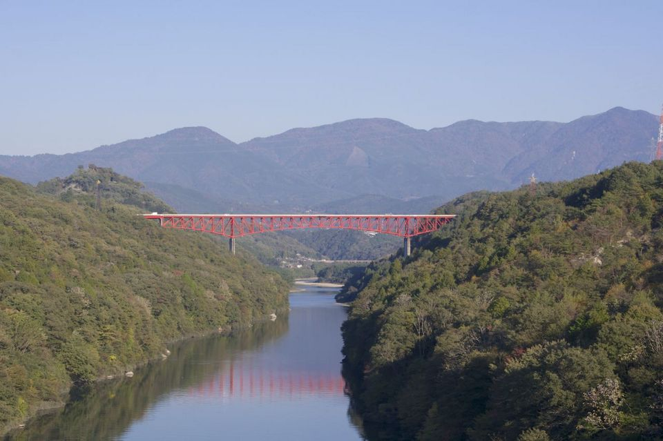 秋晴れの紺碧の空に木曽川の川面と鮮やか赤の城山大橋