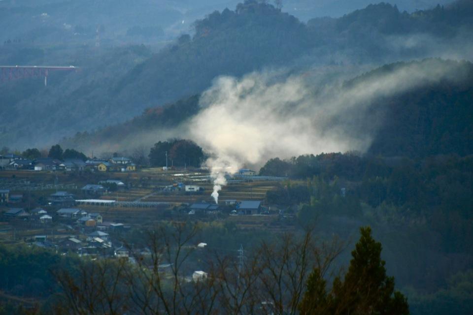 野焼きの煙たなびく幻想的な中津川の風景。