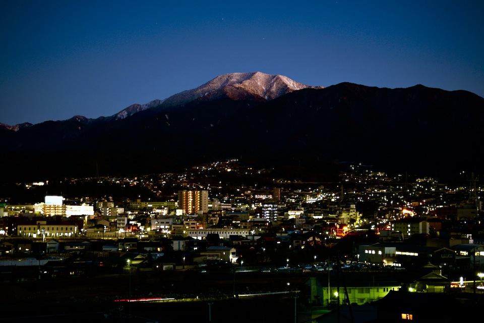 群青の夜空に浮かぶ百名山恵那山と中津川市街の夜景。 border=