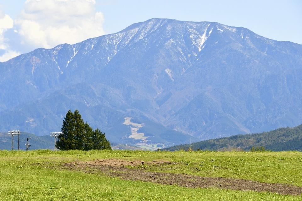 残雪の百名山恵那山と青葉若葉の椛の湖そば畑の風景。