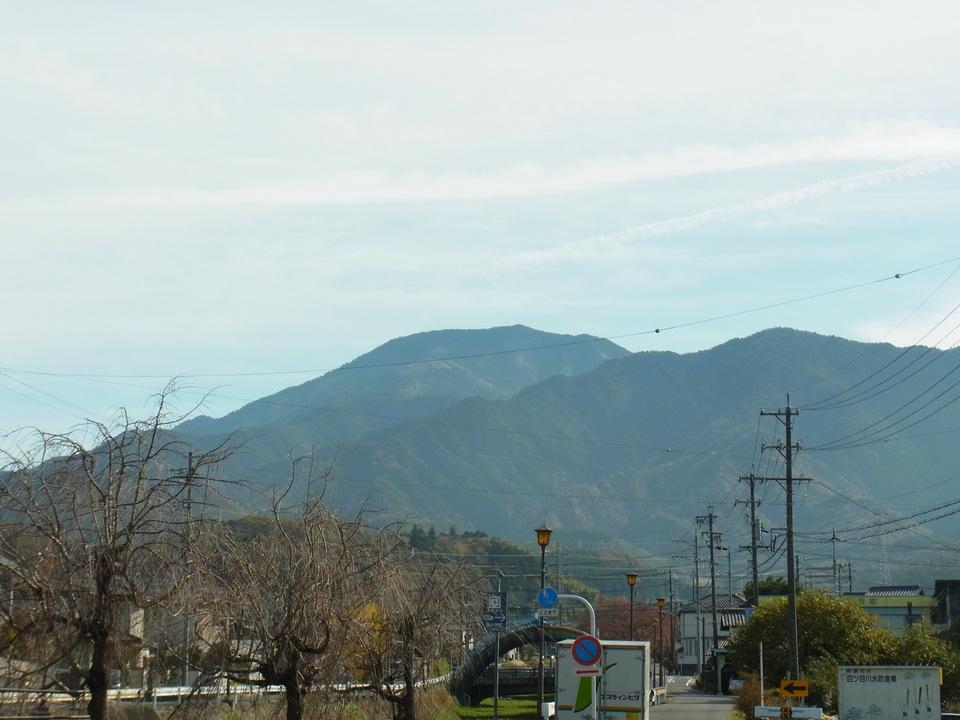消えかかった飛行機雲と恵那山
